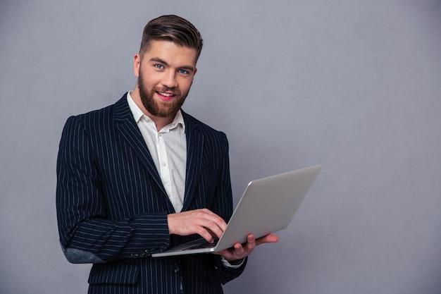 Портрет улыбающегося бизнесмена, использующего ноутбук на серой стене и смотрящего в камеру на сером фоне