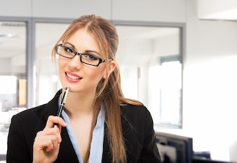 Portrait of a smiling businesswoman holding a pen in her office