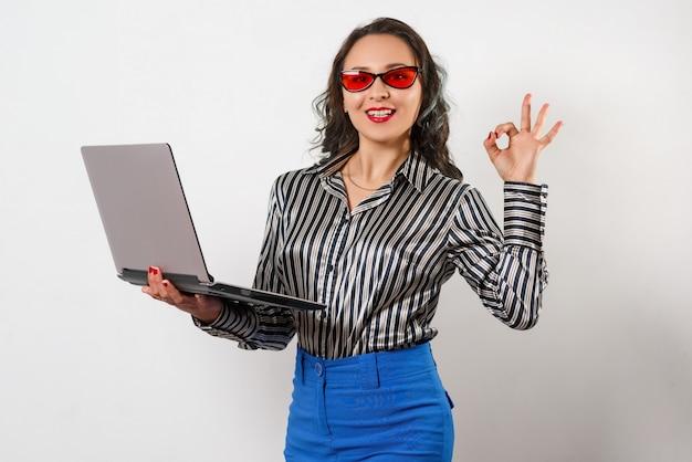 Портрет улыбающегося предприниматель держит портативный компьютер и показывает ок