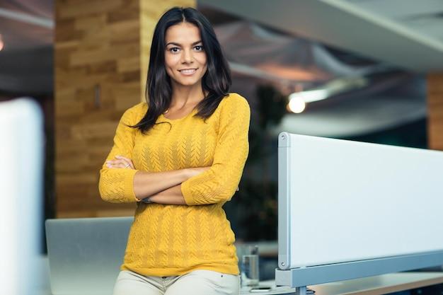 Портрет улыбающейся деловой женщины, стоящей со сложенными руками в офисе