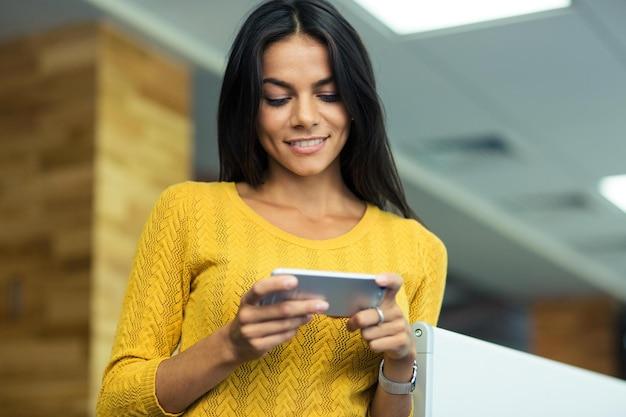 Портрет улыбающейся деловой женщины, использующей смартфон в офисе