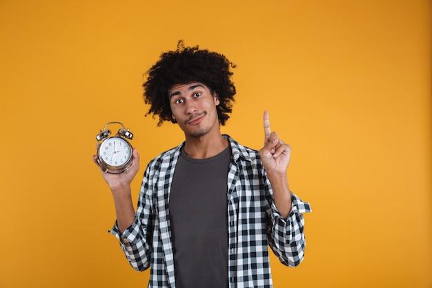 目覚まし時計を示す笑みを浮かべてカジュアルなアフリカ人の肖像画