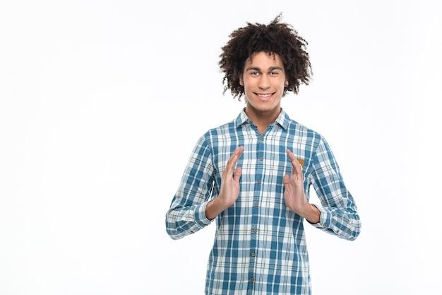 흰 벽에 고립 된 보이지 않는 뭔가를 들고 웃는 캐주얼 아프리카 계 미국인 남자의 초상화