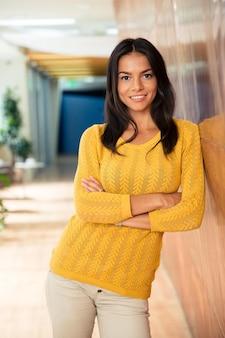 Портрет улыбающейся случайной деловой женщины, стоящей со сложенными руками в офисе