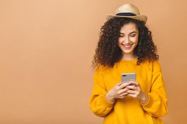 ベージュ色の背景に分離されたスマートフォンを保持している笑顔のカジュアルな巻き毛学生女性の肖像画。