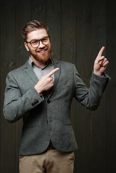 Портрет улыбающегося случайного мужчины в очках и костюме, указывающего двумя пальцами, изолированного на черном деревянном фоне