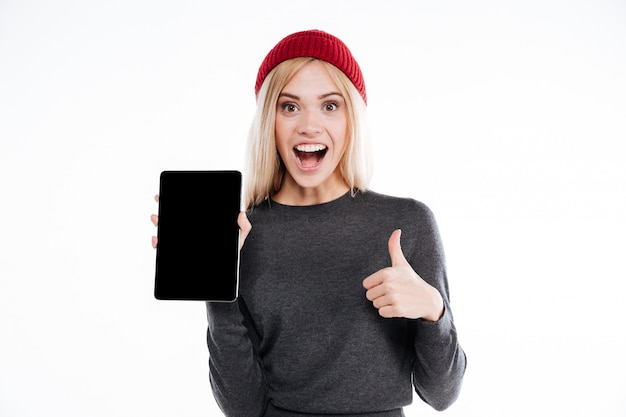 空白の画面のタブレットを保持している笑顔のカジュアルな女性の肖像画