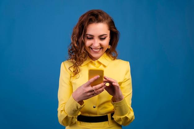 青い背景の上のスマートフォンを保持している笑顔のカジュアルな女性の肖像画。