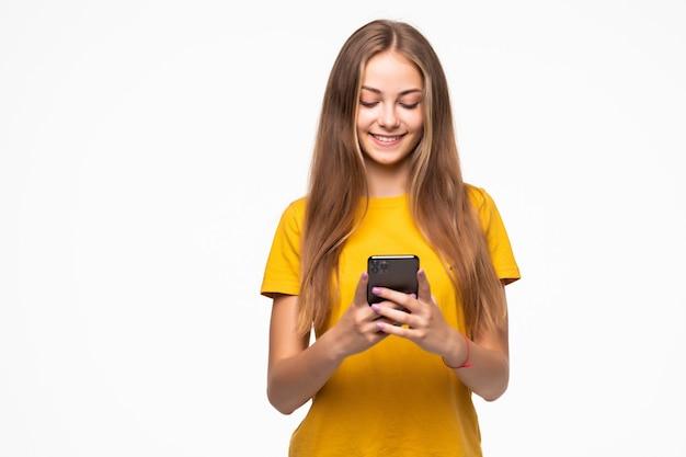 흰 벽에 스마트 폰을 들고 웃는 캐주얼 여자의 초상화
