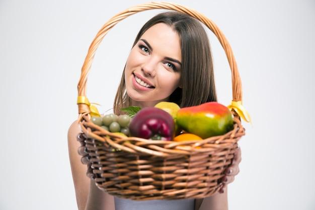 고립 된 과일 바구니를 들고 웃는 매력적인 여자의 초상화