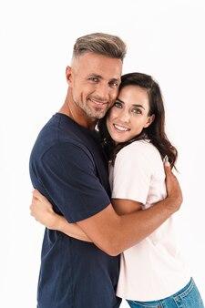 Портрет улыбающейся веселой взрослой влюбленной пары, изолированной над белой стеной.
