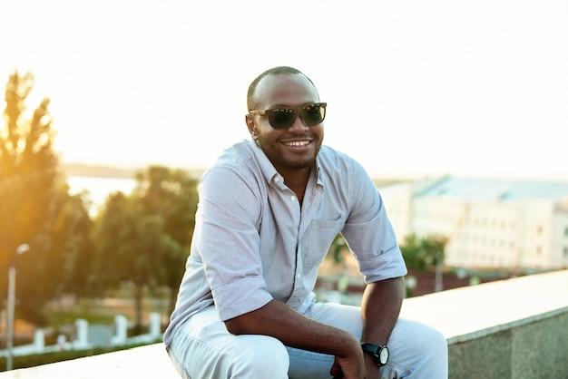 Портрет улыбающегося веселого чернокожего в солнечный день против