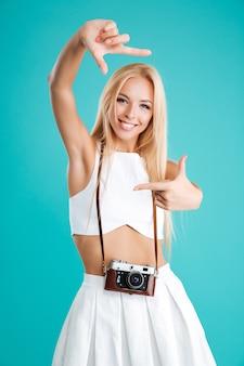 Портрет улыбающейся жизнерадостной девушки с ретро камерой, делающей жест рамки пальцами, изолированными на синем фоне
