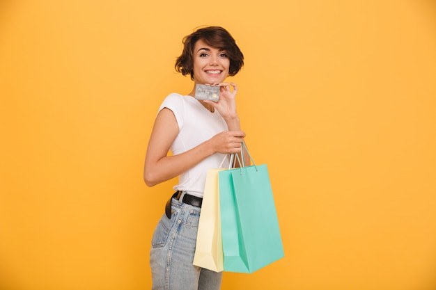 買い物袋を保持している笑顔の陽気な女性の肖像画