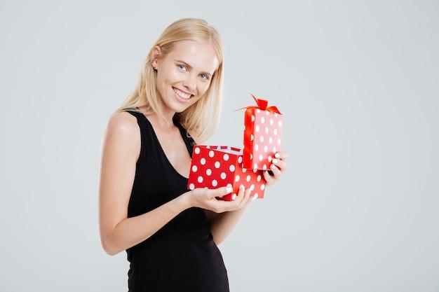 Портрет улыбающейся веселой женщины в платье, открывающей подарочную коробку, изолированную на белом фоне