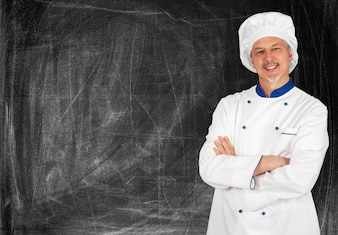 Portrait of a smiling chef in front of a blackboard