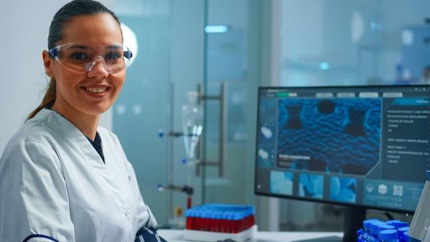 カメラを見ている実験室で安全メガネをかけている笑顔の化学者の肖像画。科学研究、ワクチンのためのハイテクおよび化学ツールを使用してウイルスの進化を調べる科学者医師のチーム