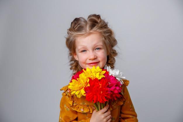 分離された花の花束と笑顔の子供のブロンドの女の子の肖像画