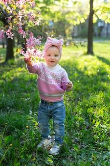 봄에 꽃이 만발한 나무의 배경에 웃는 아이(행복한 소녀)의 초상화.