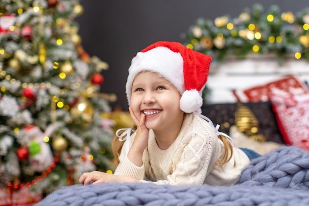 Портрет улыбающегося ребенка в канун нового года, лежащего на кровати. маленькая милая блондинка в шляпе санты, 4-летняя европейская раса. на заднем плане елка и сосновая гирлянда