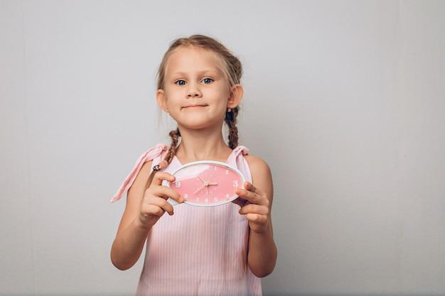 彼女の手で時計を保持し、カメラを見ている笑顔の満足している楽しい子供の肖像画。ノイズのある子供の頃のコンセプト写真