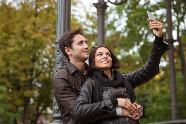 都市公園の屋外でスマートフォンで自分撮り写真を作る笑顔のカップルの肖像画
