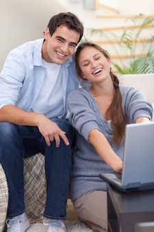 ノートパソコンを使った笑顔のカップルの肖像