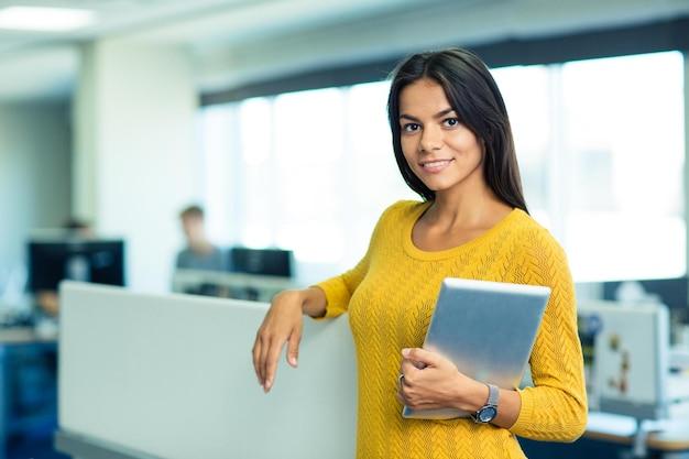 Портрет улыбающейся милой деловой женщины, стоящей с планшетным компьютером в офисе