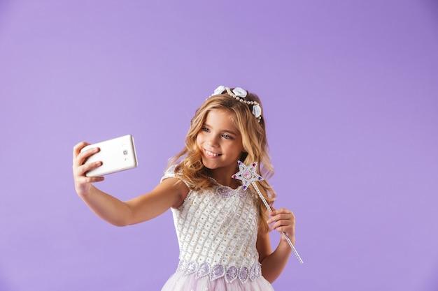 紫の壁に隔離されたプリンセスドレスに身を包んだ、魔法の杖を持って、自分撮りをしている笑顔のかわいいかわいい女の子の肖像画