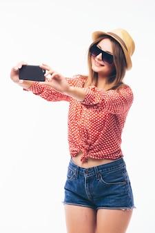 白い背景で隔離のスマートフォンでselfie写真を作る笑顔のかわいい女性の肖像画