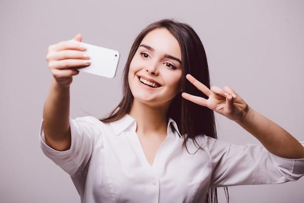 흰색 배경에 고립 된 스마트 폰에 셀카 사진을 만드는 웃는 귀여운 여자의 초상화