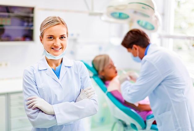 치과 의사가 배경에서 작업하는 동안 웃는 치과 의사 조수의 초상화