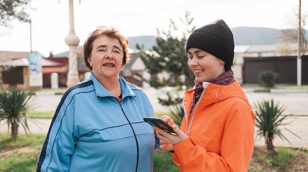 彼女の手に電話を持って笑顔の老若男女の肖像画。家族は戸外を歩きます。オンラインマップの概念。