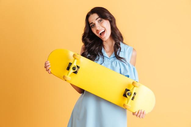 Портрет улыбающейся возбужденной брюнетки с изолированным скейтбордом