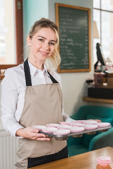 Портрет улыбающегося женского пекаря, держащего противень для выпечки кексов