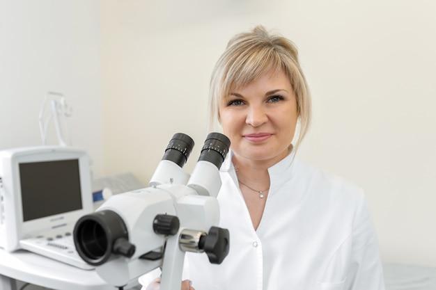 Портрет улыбающегося женского белокурого врача гинеколога возле кольпоскопа
