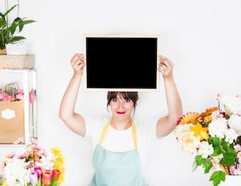 Portrait of a smiling female florist holding blank slate near fresh flowers