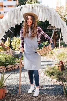 Портрет улыбающегося женщина-садовник в сером фартуке смотрит в камеру