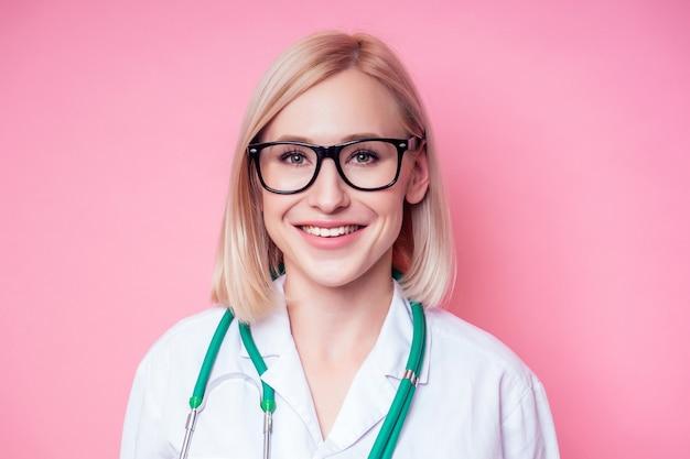 Портрет улыбающегося врача-гинеколога. красивая блондинка в белом медицинском халате и очках, держащая стетоскоп на розовом фоне в студии. идеальная кожа косметолога