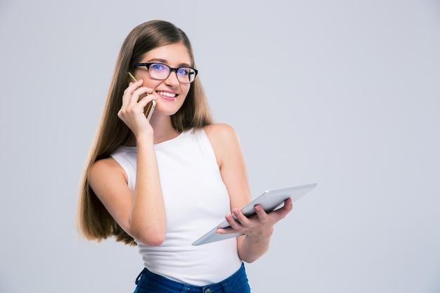 Портрет улыбающейся девушки-подростка разговаривает по телефону и с помощью планшетного компьютера изолированы