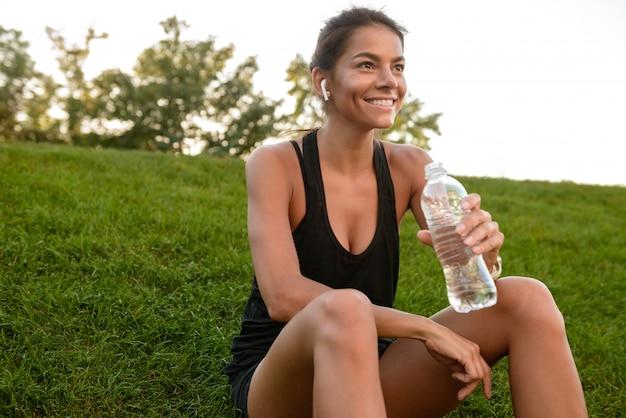 Портрет улыбающегося фитнес женщина в наушниках отдыхает