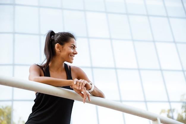 Портрет улыбающегося фитнес женщина, опираясь на рельс