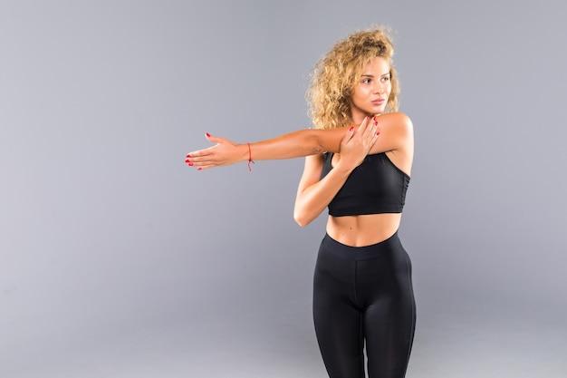 Портрет улыбающейся фитнес-женщины, протягивающей руки, изолированные на белой стене