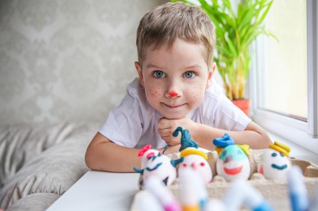 飾られたイースターエッグの前の窓辺に横たわっている塗られた顔と笑顔の4歳の少年の肖像画