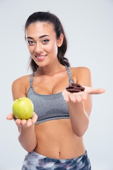 Портрет улыбающейся девушки, выбирающей между яблоком и шоколадом, изолированной на белой стене
