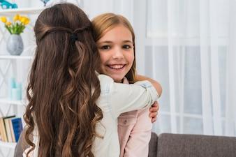 彼女の友人を自宅で抱きしめる微笑んでいる女の子の肖像画