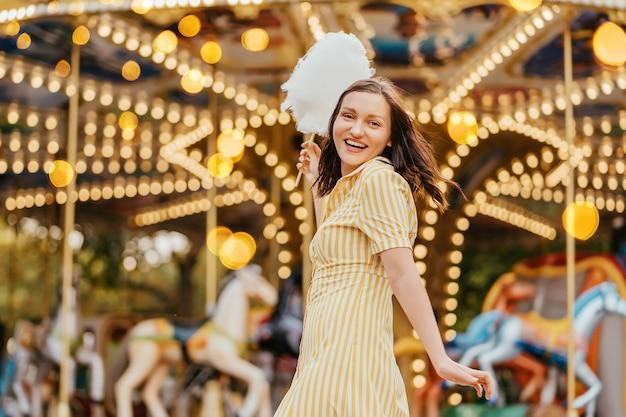 Портрет улыбающейся девушки, держащей сахарную вату перед каруселью с ночным освещением в парке развлечений.