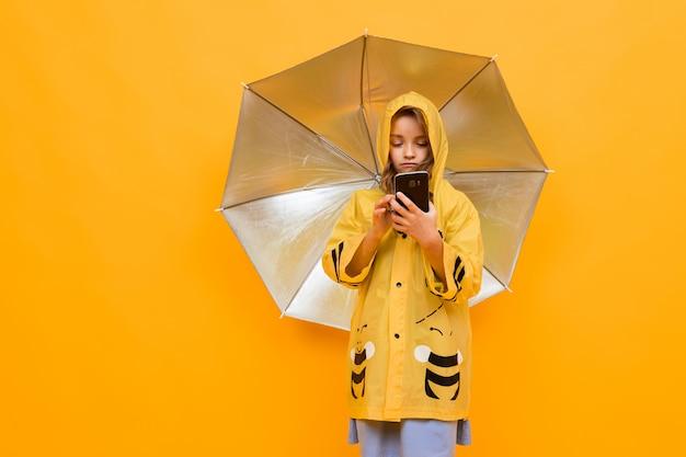 黄色の壁に銀の傘を保持している彼女の手で携帯電話を持つ美しい黄色のレインコートミツバチの笑顔の少女の肖像画