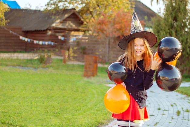 Портрет улыбающейся девушки в черной шляпе ведьмы, держащей оранжевые и черные воздушные шары на открытом воздухе, весело встречает хэллоуин.