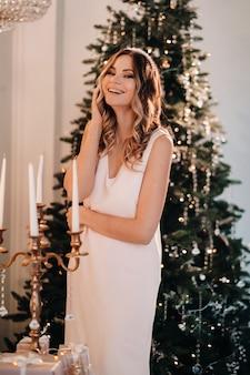 自宅のクリスマスツリーの近くにピンクのドレスを着た笑顔の女の子の肖像画。